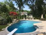 Free Form Pool with Techo Block Patio and Natural Stone Firepit